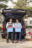 Pai e filho que desembalam o carro para a faculdade, moengas e olhando a câmera Fotografia de Stock