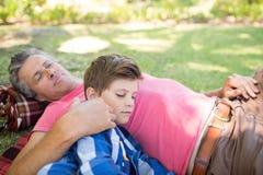 Pai e filho que dormem na cobertura do piquenique no parque imagens de stock royalty free