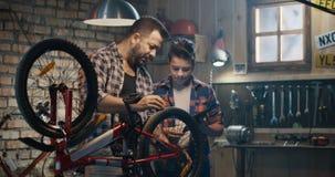 Pai e filho que falam sobre o reparo da bicicleta vídeos de arquivo