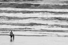 Pai e filho que guardam as mãos na praia no Oceano Pacífico no por do sol com ondas foto de stock