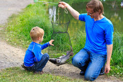Pai e filho que guardam peixes que travaram Fotografia de Stock Royalty Free