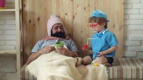 Pai e filho que jogam a clínica em casa Conceito médico da educação Doutor com estetoscópio que examina o homem farpado Criança e