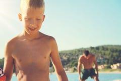 Pai e filho que jogam com uma bola no bach perto do mar Homem e menino contra o oceano, férias ativas das férias de verão Imagem de Stock Royalty Free