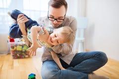 Pai e filho que jogam e que têm o divertimento em casa Fotografia de Stock Royalty Free