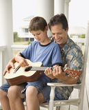 Pai e filho que jogam a guitarra Fotos de Stock Royalty Free