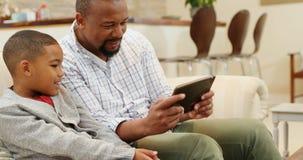 Pai e filho que jogam jogos na tabuleta digital na sala de visitas 4k filme