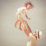 Pai e filho que jogam na praia no tempo do dia Imagem de Stock Royalty Free