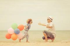 Pai e filho que jogam na praia no tempo do dia Fotos de Stock Royalty Free