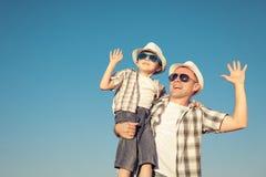 Pai e filho que jogam no campo no tempo do dia Fotografia de Stock