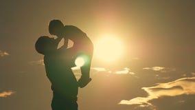 Pai e filho que jogam no parque na silhueta do por do sol de uma família feliz filme