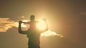 Pai e filho que jogam no parque na silhueta do por do sol de uma família feliz vídeos de arquivo