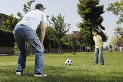Pai e filho que jogam o futebol Fotografia de Stock Royalty Free
