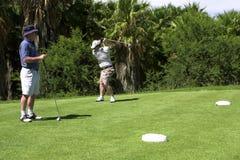 Pai e filho que jogam o golfe. Imagem de Stock