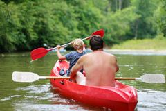 Pai e filho que kayaking no rio fotografia de stock