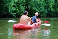 Pai e filho que kayaking no rio foto de stock royalty free