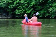 Pai e filho que kayaking no rio imagem de stock