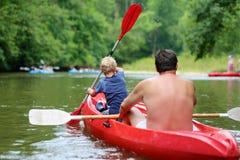 Pai e filho que kayaking no rio imagens de stock