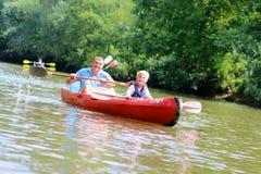 Pai e filho que kayaking no rio fotografia de stock royalty free
