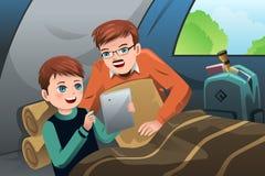Pai e filho que leem um PC da tabuleta em uma barraca de acampamento Imagens de Stock