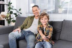 pai e filho que olham a tevê junto ao descansar no sofá foto de stock royalty free
