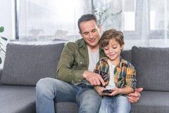 pai e filho que olham a tevê junto ao descansar no sofá foto de stock