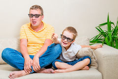 Pai e filho que olham um filme engraçado na tevê Imagens de Stock