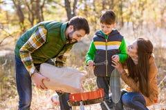 Pai e filho que põem carvões na grade fotografia de stock