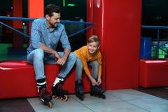 Pai e filho que põem sobre patins de rolo foto de stock
