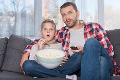Pai e filho que prestam atenção à tevê Fotos de Stock Royalty Free
