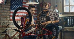 Pai e filho que reparam uma bicicleta em uma garagem video estoque