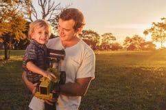 Pai e filho que riem junto em um por do sol bonito em um parque imagens de stock royalty free