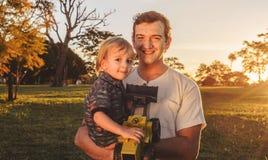 Pai e filho que riem junto em um por do sol bonito em um parque Foto de Stock Royalty Free