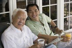Pai e filho que sentam-se fora da HOME imagens de stock