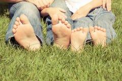 Pai e filho que sentam-se na grama no tempo do dia Imagens de Stock