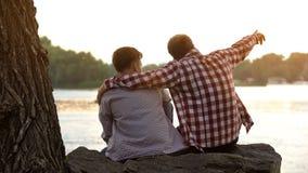 Pai e filho que sentam-se no banco de rio, paizinho que aponta na distância, apreciando a vista fotos de stock