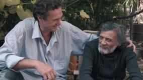 Pai e filho que sentam-se no banco que ri e que balança Grisalho e novo video estoque