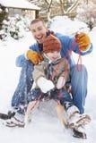 Pai e filho que sentam-se no Sledge Foto de Stock