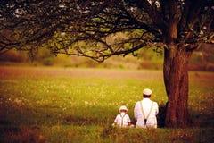 Pai e filho que sentam-se sob a árvore no gramado da mola imagem de stock royalty free