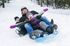 Pai e filho que sledding no tempo de inverno Fotos de Stock Royalty Free
