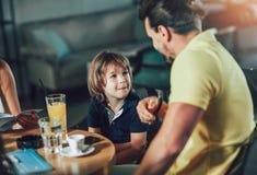 Pai e filho que têm o divertimento em um restaurante imagens de stock