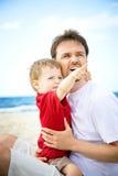 Pai e filho que têm o divertimento na praia. fotografia de stock royalty free