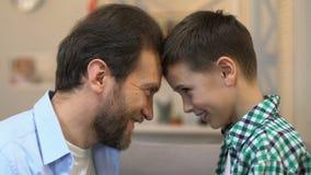 Pai e filho que tocam nas testas, na unidade e no apoio, relações amigáveis filme