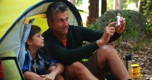 Pai e filho que tomam um selfie no telefone celular fora da barraca video estoque