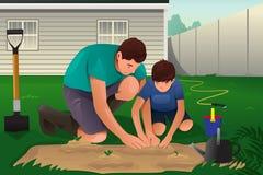 Pai e filho que trabalham em um jardim Fotos de Stock Royalty Free