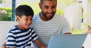 Pai e filho que usa o portátil 4k video estoque