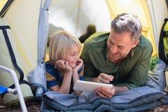Pai e filho que usa a tabuleta digital ao descansar no acampamento imagem de stock royalty free
