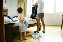 Pai e filho que vestem sua roupa na pressa e na precipitação foto de stock royalty free