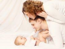 Pai e mãe felizes com o bebê na casa da cama Imagens de Stock Royalty Free