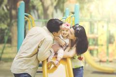 Pai e mãe que beijam a filha em corrediças imagem de stock