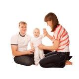 Pai e matriz que vestem o bebê. Fotografia de Stock Royalty Free